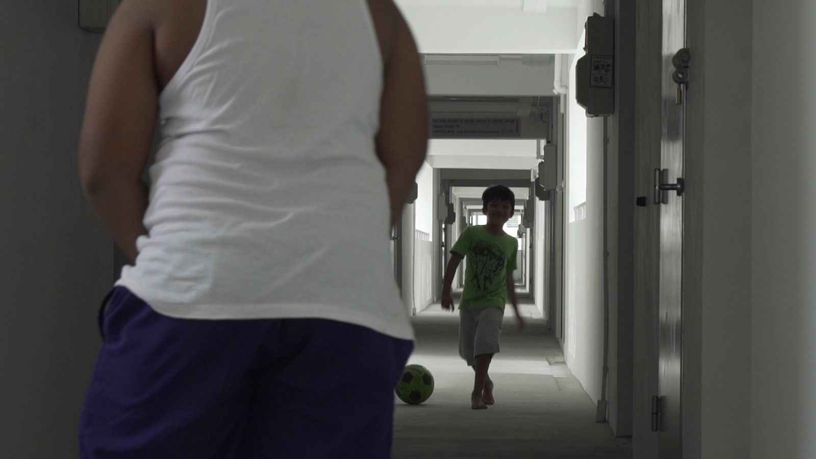 Fizah's children playing football in the corridor