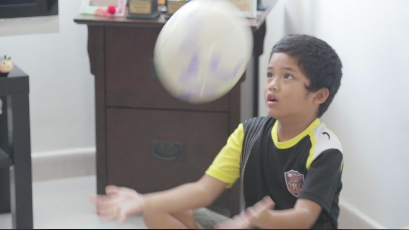 One of Fizah's children juggling a ball in the house